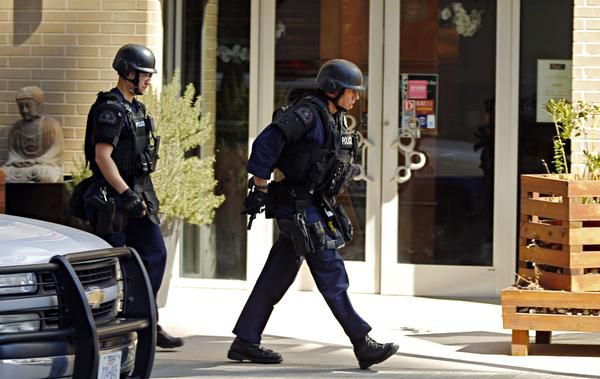 Police officers walked around a corner during the standoff. Much of Victory Park and the surrounding area was put on lockdown, including two schools, the AT&T Performing Arts Center, the Perot Museum and the Dallas World Aquarium.