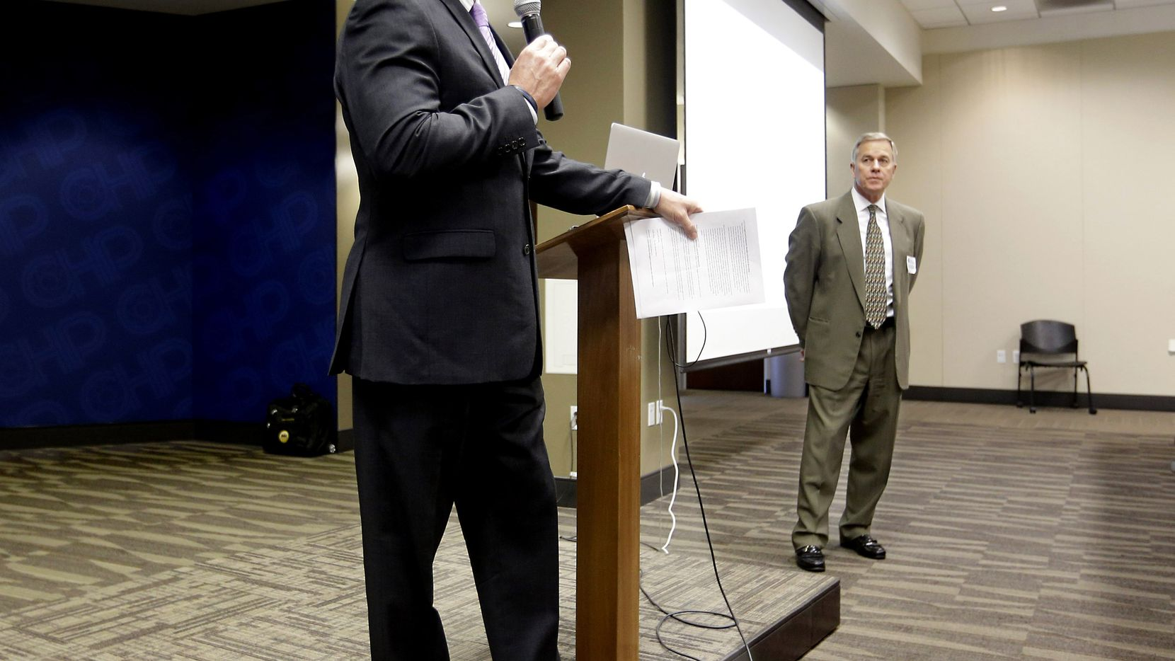 In this photo taken Thursday, Feb. 19, 2015, retired Fort Worth Police Chief Jeffery Halstead, left, introduces retired Cincinnati Police Chief Tom Streicher, during a presentation at a conference hosted by Taser International at the California Highway Patrol Headquarters in Sacramento, Calif.  Halstead successfully pushed the city of Fort Worth to approve a no-bid contract worth up $2.7 to purchase body cameras from Taser, the stun-gun maker that is now the leading supplier of body cameras for police. A review by The Associated Press shows Taser is covering airfare and hotel stays for police chiefs who travel to speak at the company's marketing conferences. It is also hiring some recently retired chiefs as consultants, sometimes months after their cities signed contracts with Taser.(AP Photo/Rich Pedroncelli)