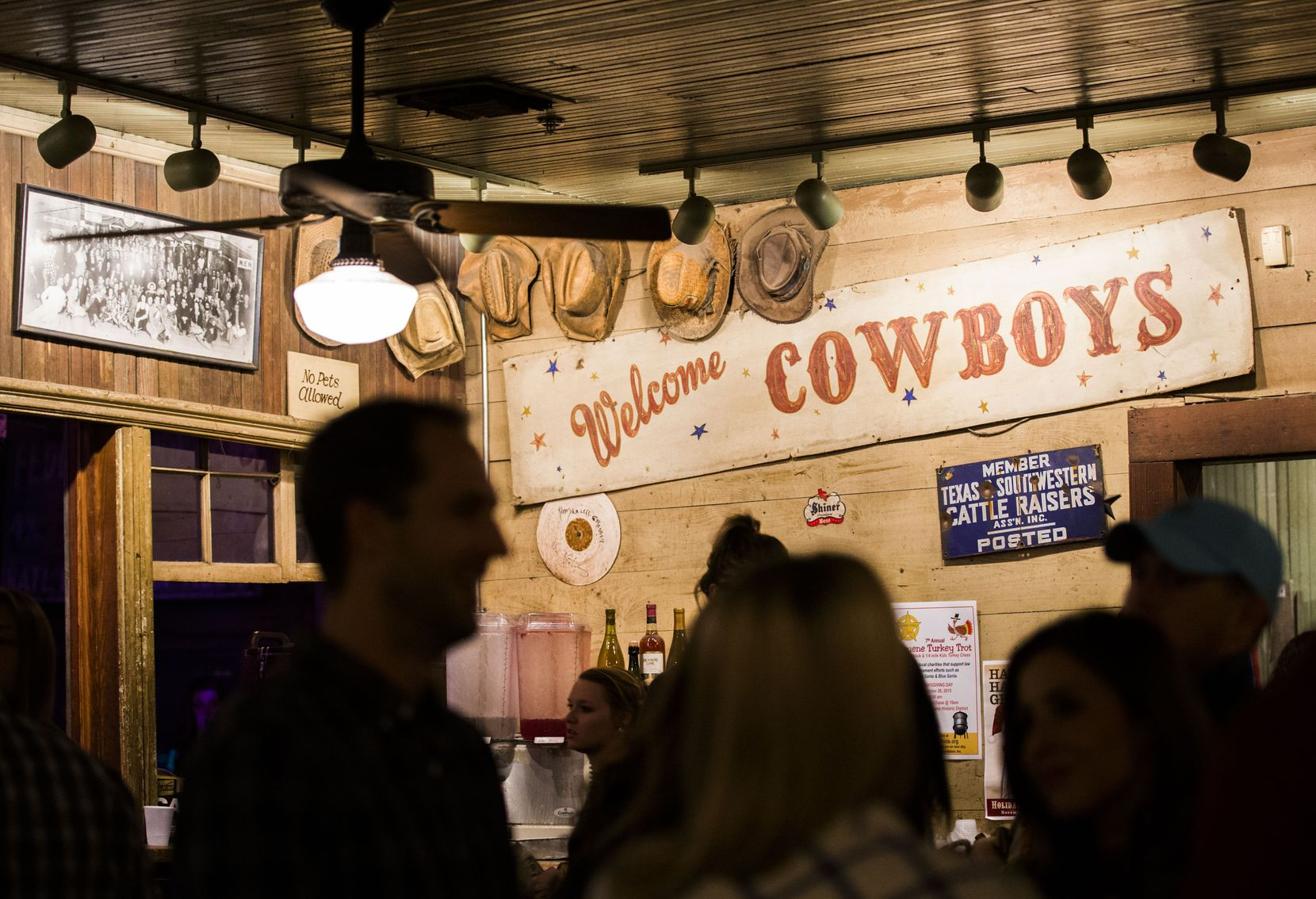 "A ""Welcome Cowboys"" sign is displayed above the bar at Gruene Hall, shown in 2015."