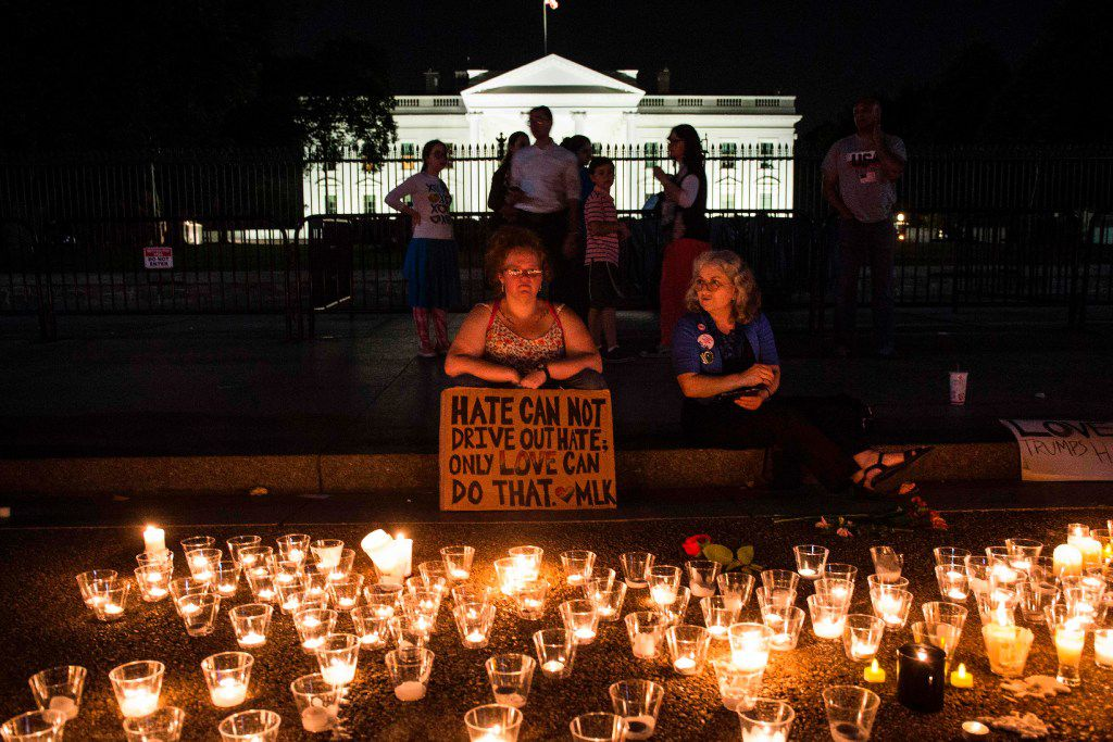 """TOPSHOT - People gather in front of the White House on August 13, 2017 in Washington, DC for a vigil in response to the death of a counter-protestor in the August 12th """"Unite the Right"""" rally the turned violent in Charlottesville, Virginia.   A woman died and 19 injured in the city of Charlottesville when a car plowed into a crowd of people after a rally by Ku Klux Klan members and other white nationalists turned violent. Two state police officers died in a helicopter crash near the area. / AFP PHOTO / ZACH GIBSONZACH GIBSON/AFP/Getty Images"""