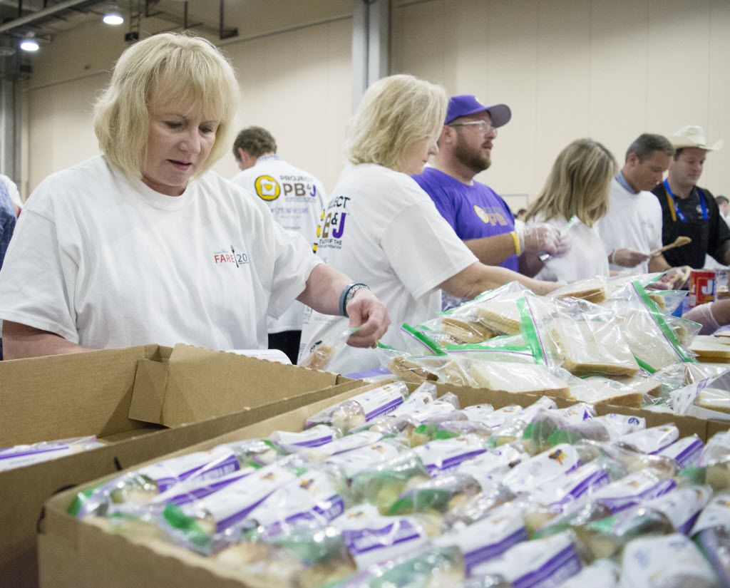 Surrounded by boxes and piles of PB&J sandwiches, Spread the Love volunteer Vickie Grimes tapes PB&J sandwich bags closed with 25 minutes left in the one hour Guinness World Record Spreading Party.