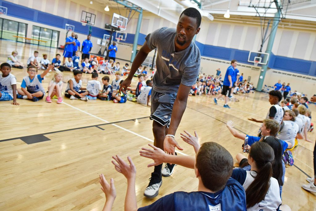Mavericks forward Harrison Barnes runs down an aisle of kids slapping their hands before leaving this year's Mavs Basketball Academy Hoop Camp in July at Prestonwood Sports & Fitness Center in Plano. The camp hosted fun basketball activities for kids ages 8-18 to learn the fundamentals of the game and learn sportsmanship. (Ben Torres/Special Contributor)