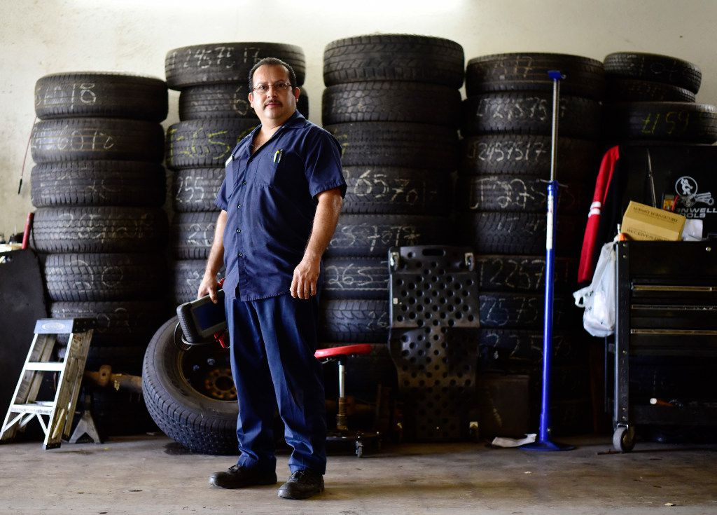 Joaquin Godinez poses at his auto mechanic shop in southeast Dallas.