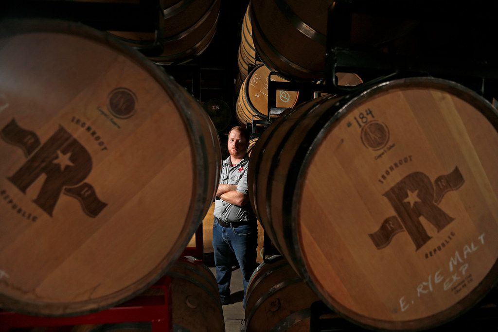 Co-owner Robert Likarish poses for a photograph with barrels of whiskey in the distillery at Ironroot Republic Distilling in Denison, Texas. (Jae S. Lee/The Dallas Morning News)