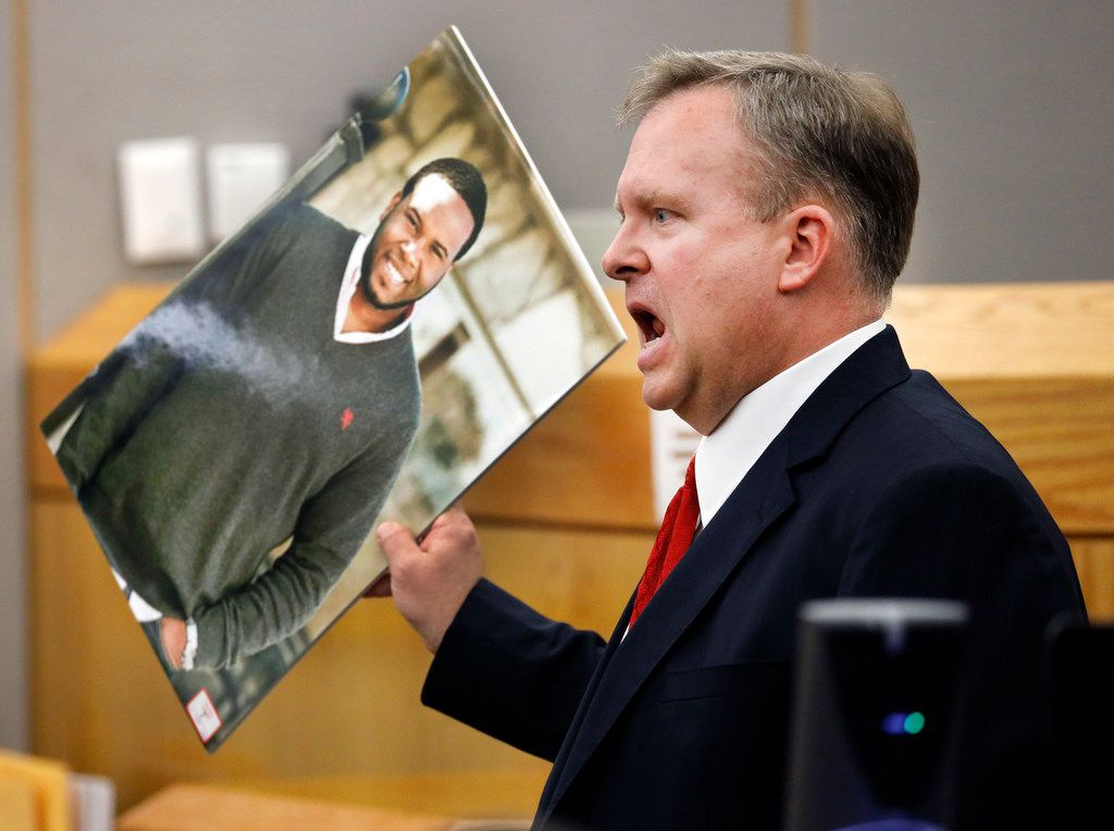 Assistant District Attorney Jason Hermus waves a photo of Botham Jean at the jury as he presents his closing arguments in Amber Guyger's murder trial in the 204th District Court at the Frank Crowley Courts Building in Dallas, Monday, September 30, 2019. The jury convicted fired Dallas police Officer Guyger of murder on Tuesday.