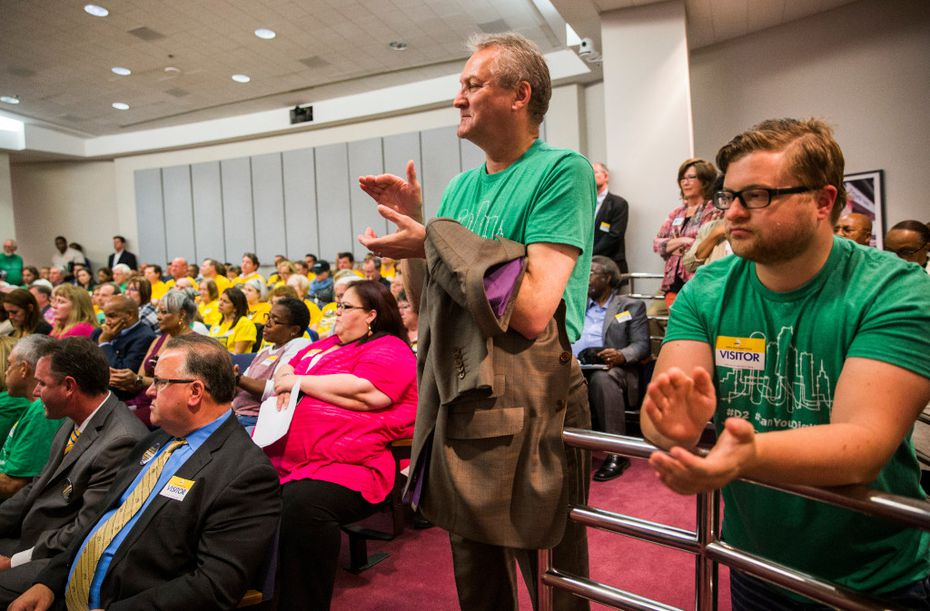 Lawrence Sweeny, center, and Ryan Roskey, right, applaud during public comment before the board of the Dallas Area Rapid Transit before they voted on a rail corridor plan on Tuesday, October 25, 2016 at DART headquarters in Dallas. The board voted to finance both the Cotton Belt and D2 subway.