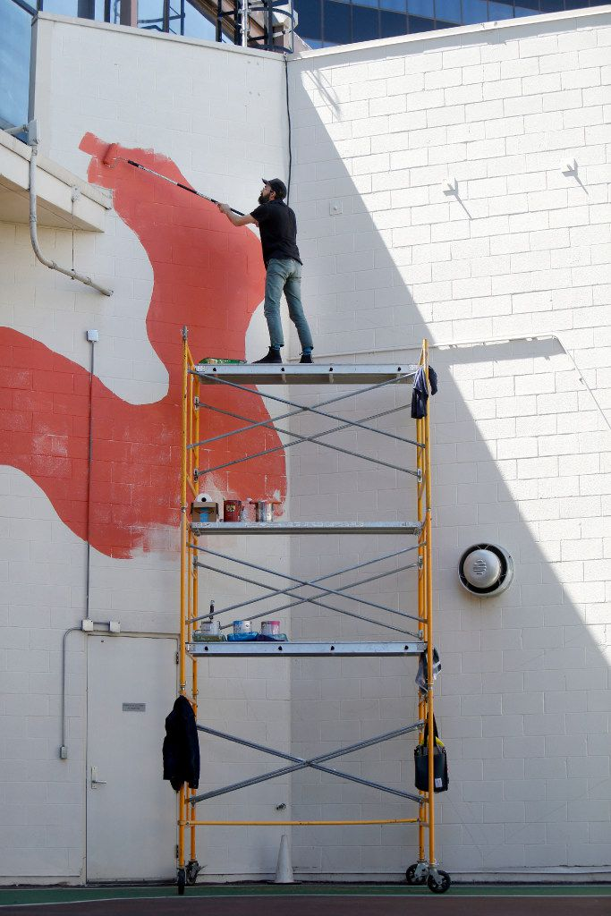 Kyle Steed works on his mural at the Plaza of the Americas.