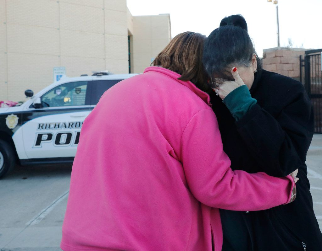 Terri Mull, left, consoles Karen Yells, both Richardson ISD crossing guards, after placing flowers on a police car in front of the Richardson, Texas police headquarters on Thursday, Feb. 8, 2018. A Richardson police officer was fatally shot the night before at an apartment complex. A second person, 30-year-old Rene Gamez, who lived in the apartment complex, also died, police said. The suspect was identified Thursday as Brandon McCall. He is being held in the Collin County jail on a charge of capital murder of a police officer.