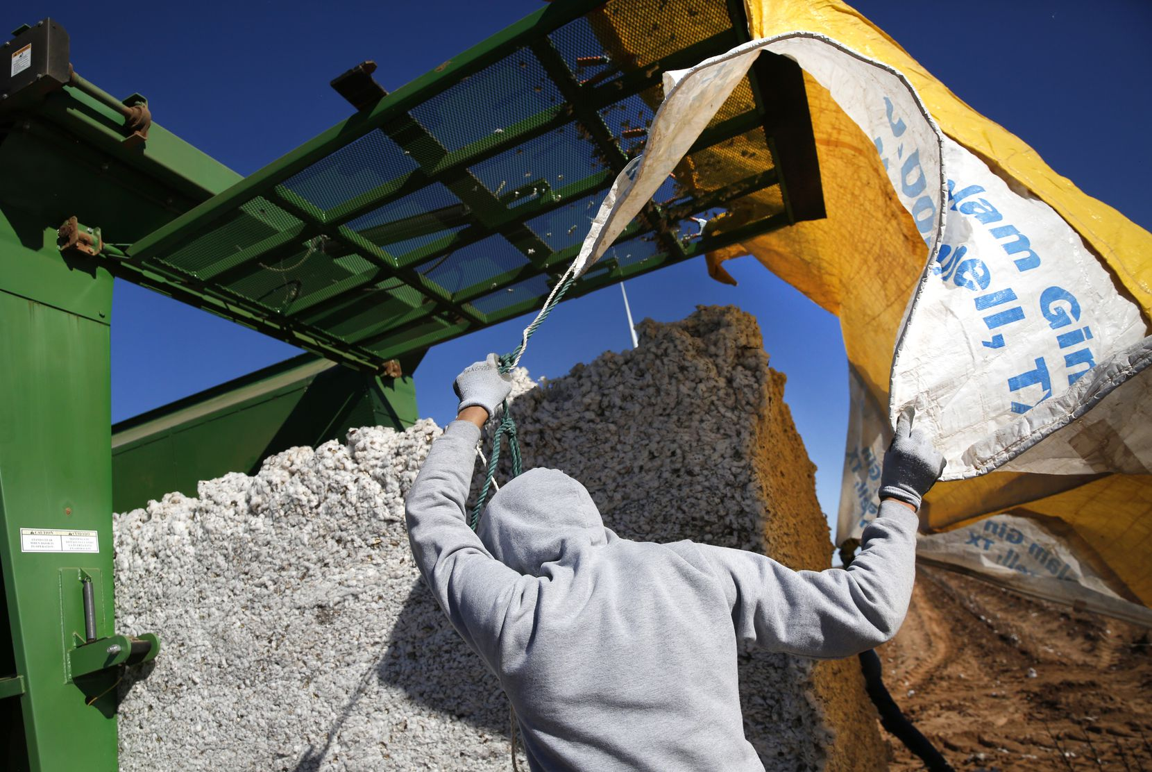 Charles Johnson pulls a tarp over a bale of cotton during the harvest at Matt Farmer's farm in Lynn County.