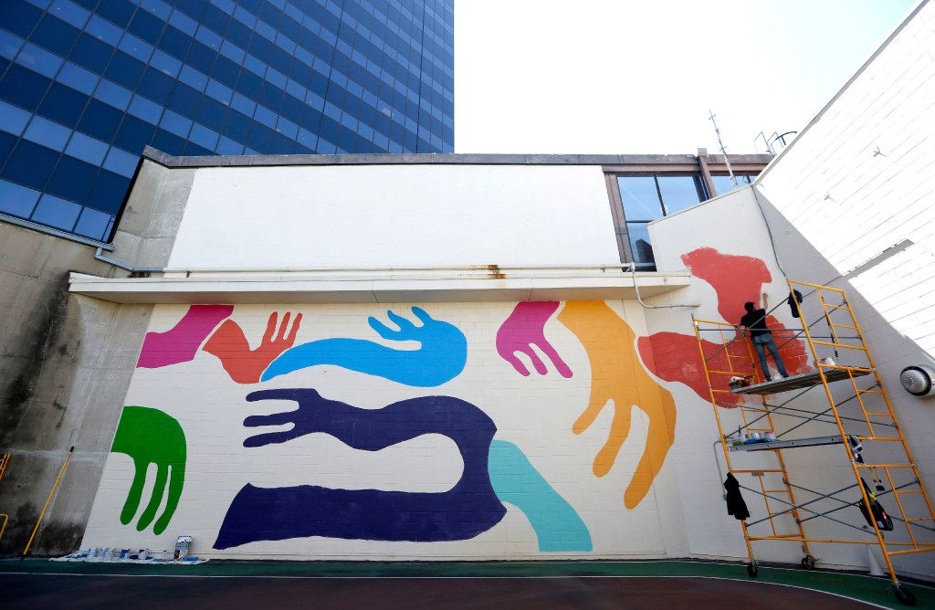 Kyle Steed works on his mural at the Plaza of the Americas building in downtown Dallas. (Rose Baca/The Dallas Morning News)