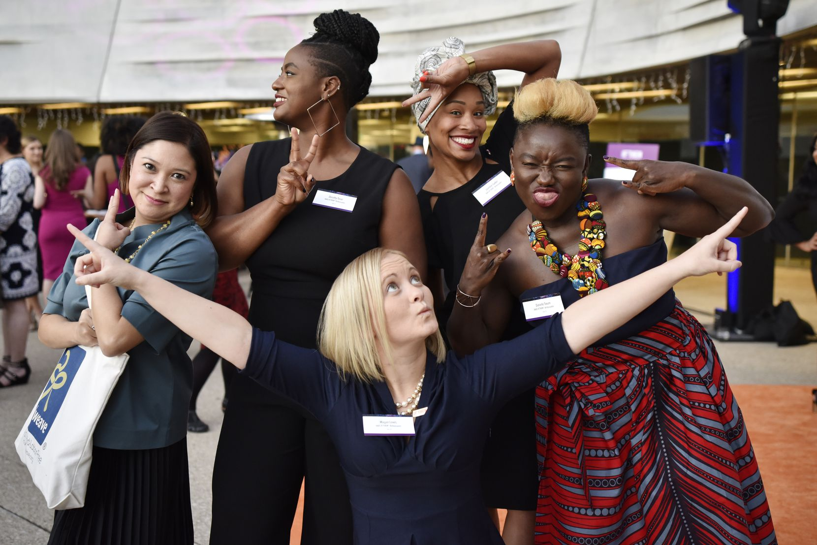 """IF/THEN Ambassadors (L-R) Charita Castro, Dorothy Tovar, Megan Lewis, Jasmine Sadler and Danielle Twum, far-right, strike their best yet funniest pose during a red carpet event for the IF/THEN Ambassador Summit """"An Evening of Science and Storytelling,"""" at the Perot Museum."""