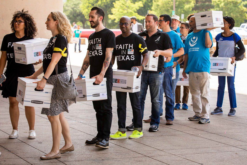 A coalition of labor and faith groups and political activists waits in the security line to enter City Hall to deliver petitions calling for a city ordinance mandating paid sick time to be placed on the November ballot on Monday, June 11, 2018, in Dallas.