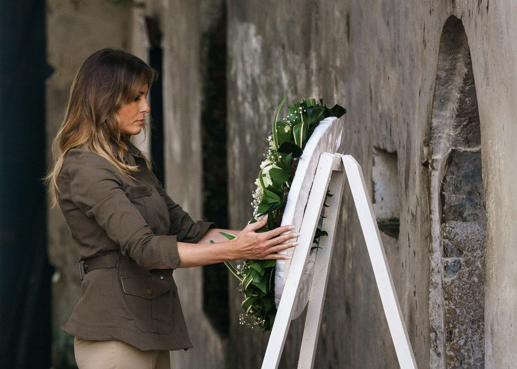 """First lady Melania Trump places a wreath at one of the dungeon doors at Cape Coast Castle in Cape Coast, Ghana, Wednesday, Oct. 3, 2018. Cape Coast Castle was a """"slave castle"""" used in the trans-Atlantic slave trade. Mrs. Trump is visiting Africa on her first solo international trip."""