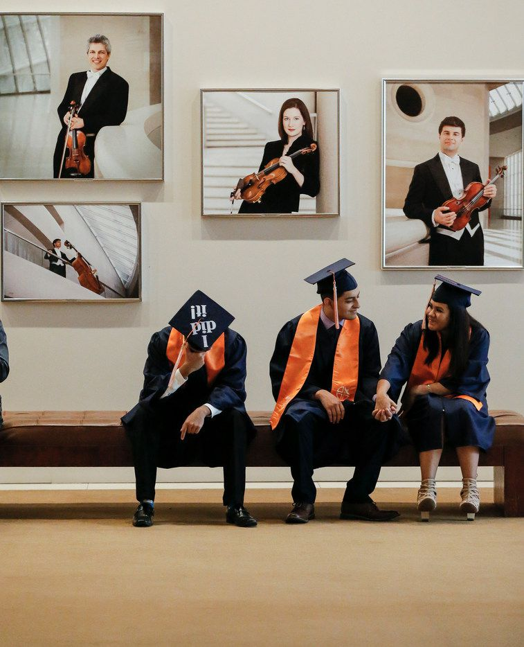 "Sitting under portraits of professional musicians, (L to R) Isaac Gonzales, Juan Ruiz and Jazmin Moctezuma, members of the first graduating class of Cristo Rey Dallas College Prep, wait for the start of their graduation ceremony at the Meyerson in Dallas, Sunday, June 2, 2019. Written on the top of the mortarboard of Gonzales' cap were the words ""I did it."""
