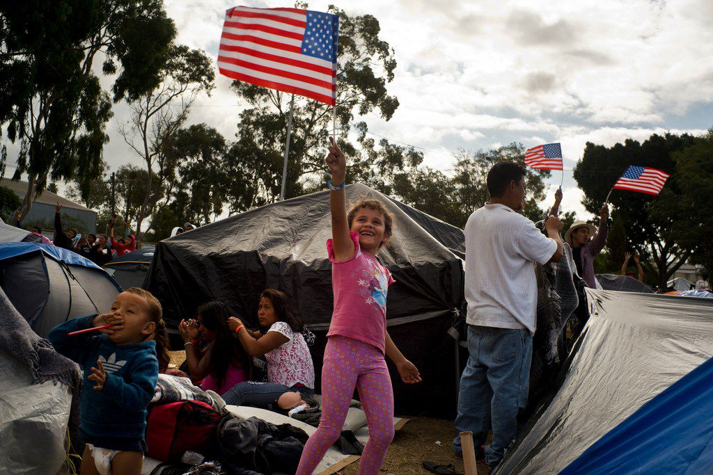 Honduran migrant Genesis Belen Mejia Flores, 7, waves an American flag at two U.S. border control helicopters flying overhead near a shelter in Tijuana, Mexico on Nov. 24, 2018.