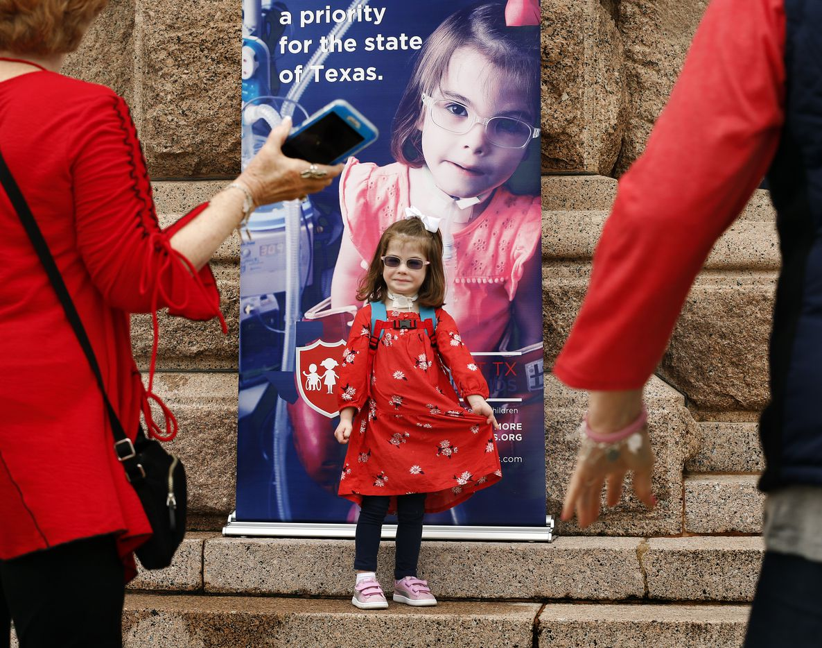 Tina Gregory, daughter of David and Natalie Gregory of Southlake, Texas, is shy about standing next to a larger-than-life poster of herself during a Protect Fragile TX Children rally outside the Texas State Capitol, Tuesday, February 26, 2019.