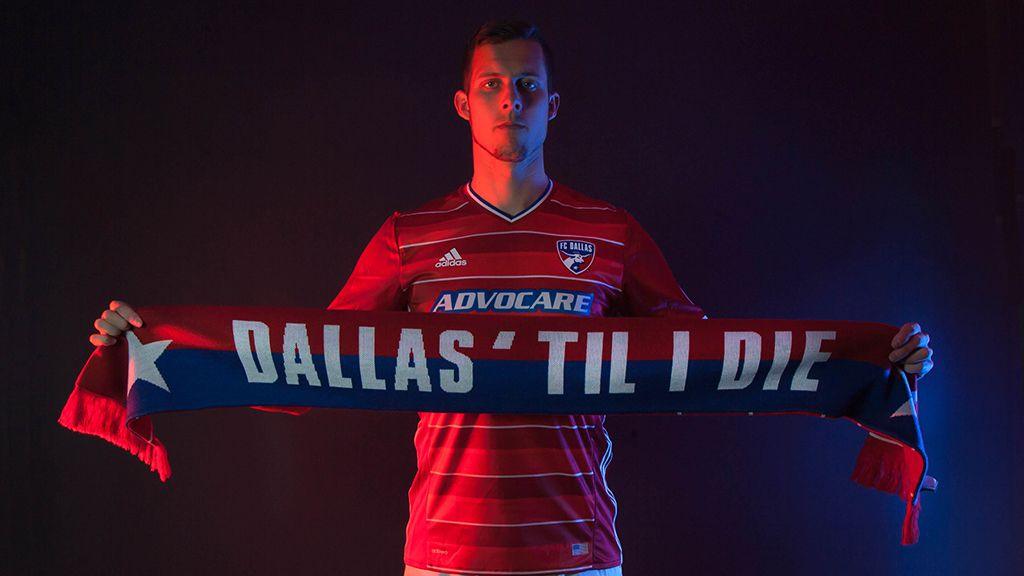 Matt Hedges holds up a scarf with the local fan slogan, Dallas 'Til I Die.