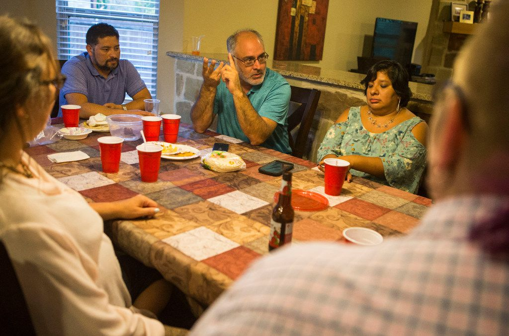 From left: Mario Castro, David Venegas and Melissa Baize, all parents of transgender children, surround the kitchen table in discussion on July 7, 2017, in Little Elm.