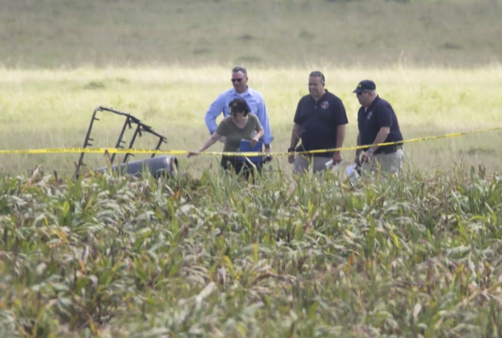 """The partial frame of a hot air balloon is visible above a crop field as investigators comb the wreckage of a crash Saturday morning, July 30, 2016. Authorities say the accident caused a """"significant loss of life."""""""