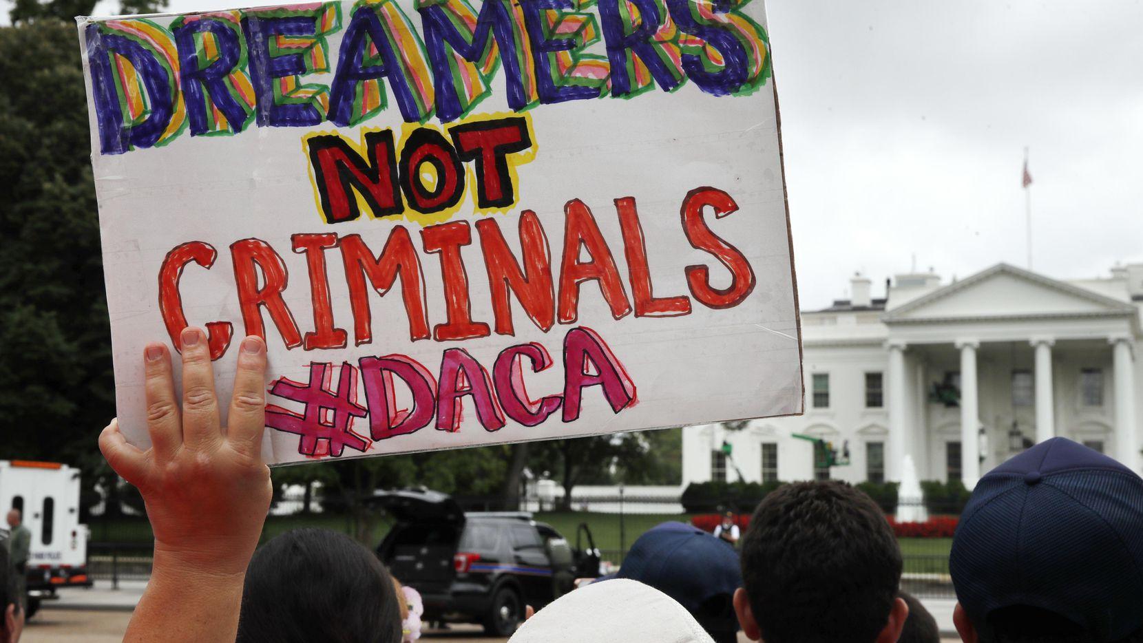 Una mujer sostiene un cartel frente de apoyo a DACA a la Casa Blanca. AP