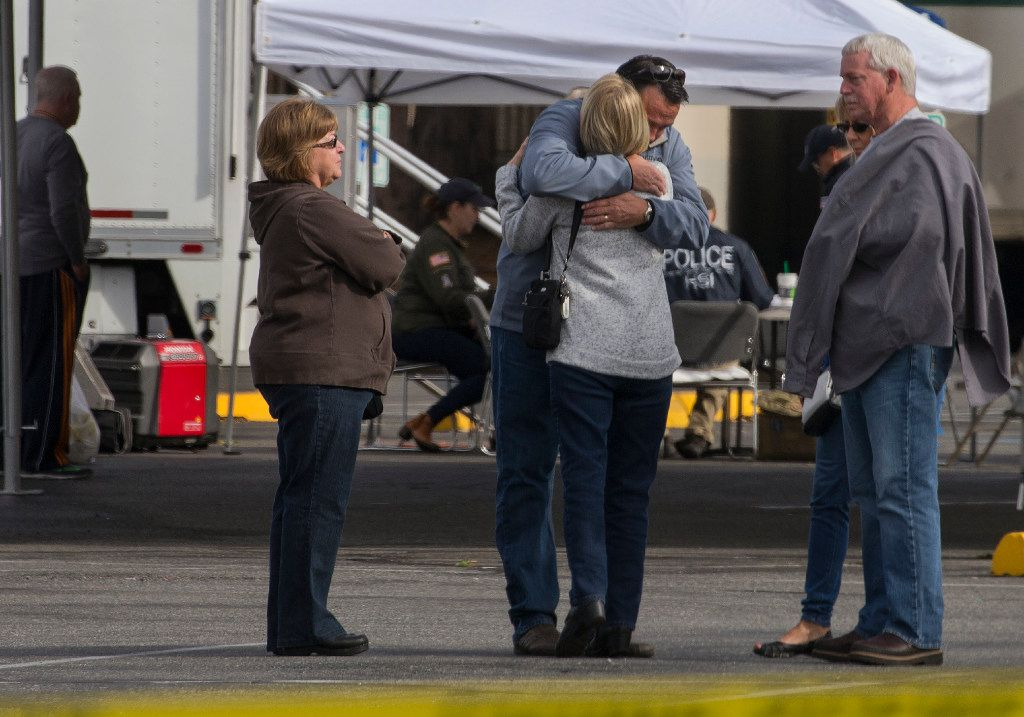 Burlington Mayor Steve Sexton hugs one of the victims' family members outside Cascade Mall.