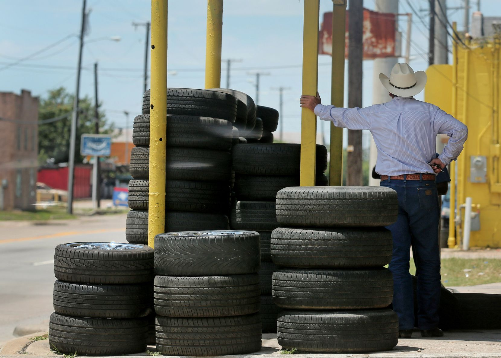 A tire shop employee awaits customers on Singleton Boulevard in West Dallas.