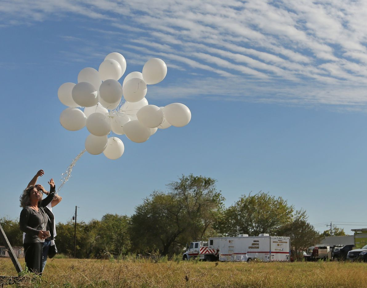 Malinda Lamford, left, and Michelle Trigo release 26 balloons in tribute to those killed at the First Baptist Church of Sutherland Springs in Sutherland Springs, Texas. At least 26 people died Sunday after a gunman opened fire at a Baptist church in the small town southeast of San Antonio. Photographed on Monday, November 5, 2017. (Louis DeLuca/The Dallas Morning News)