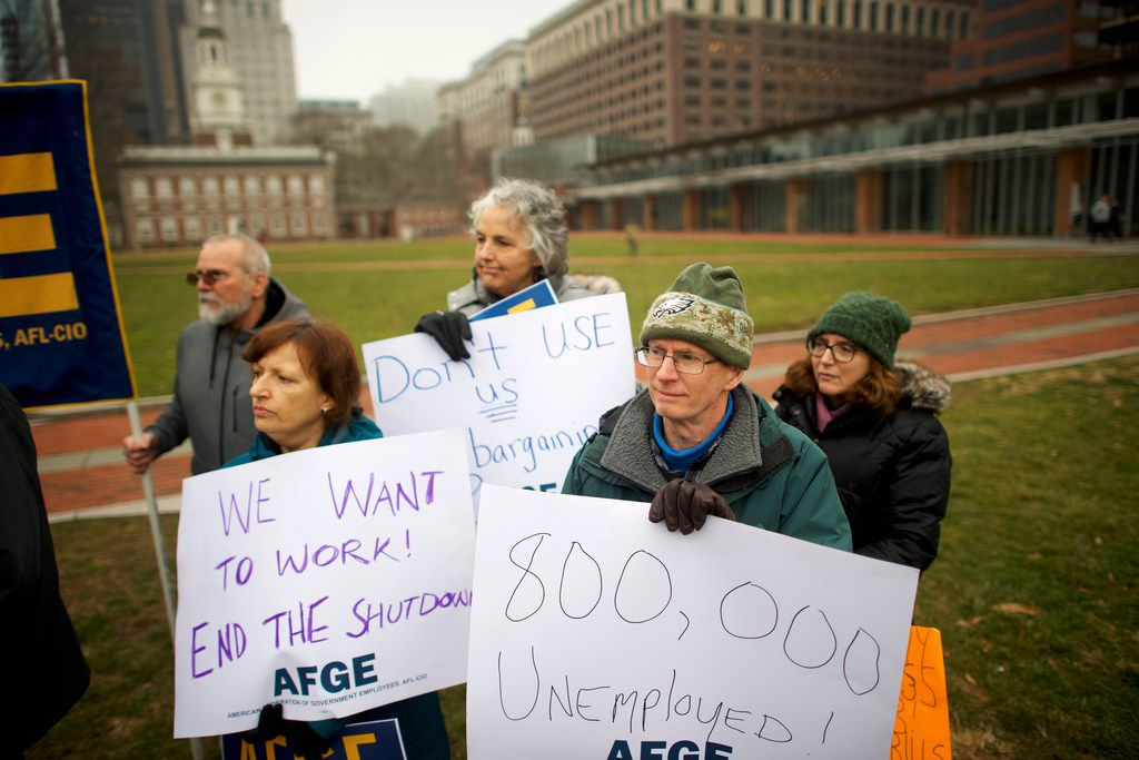 "Mark Cosgrove, 64, a park ranger for 30 years, holds a placard stating ""800,000 unemployed!"" joining fellow furloughed federal workers and area elected officials at a protest rally in front of Independence Hall on Jan. 8, 2019 in Philadelphia, Pa."