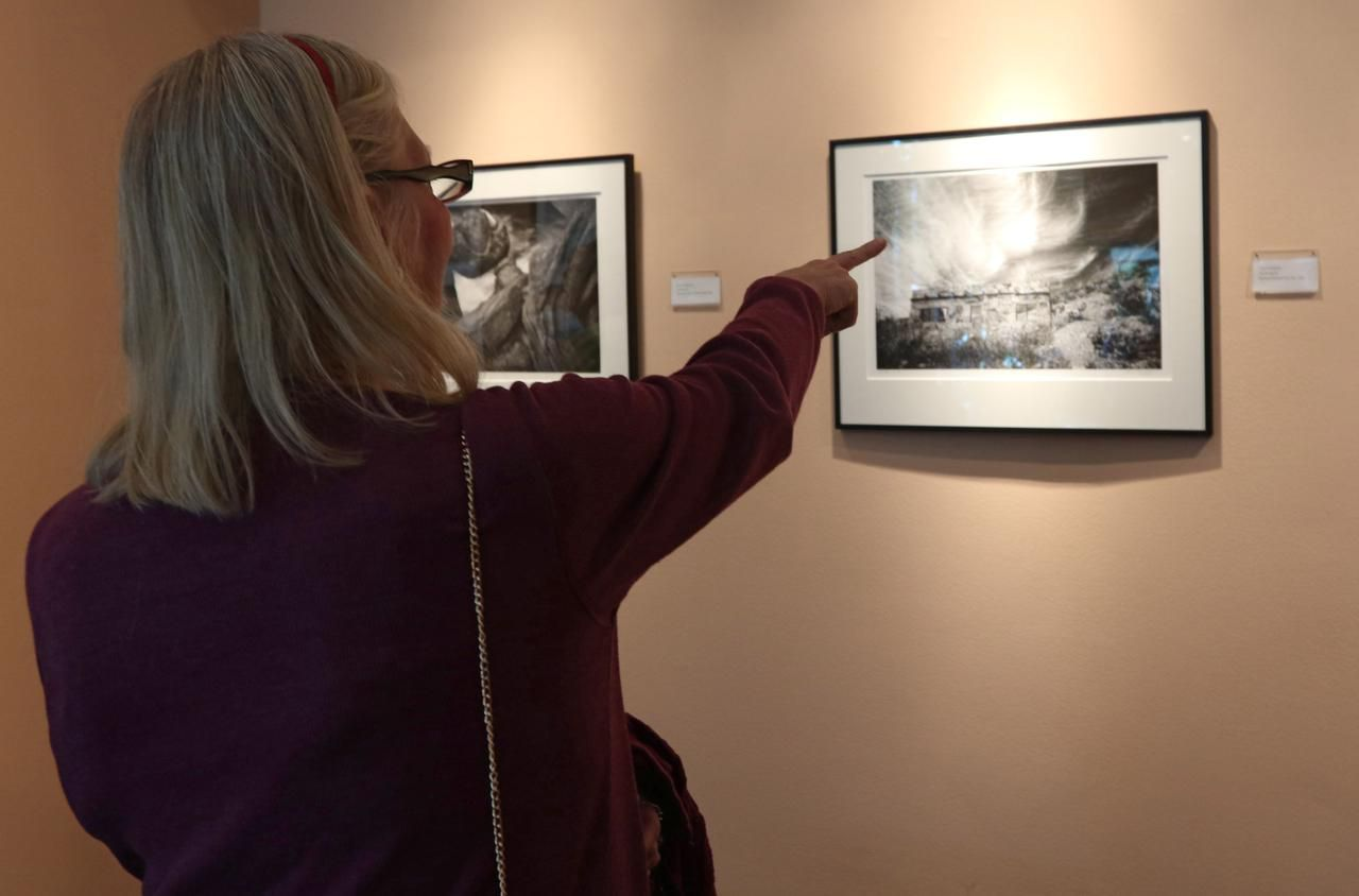 Sandy Faltermeier of Dallas points at one of Terry Cockerham photographs at the Irving Arts Center.
