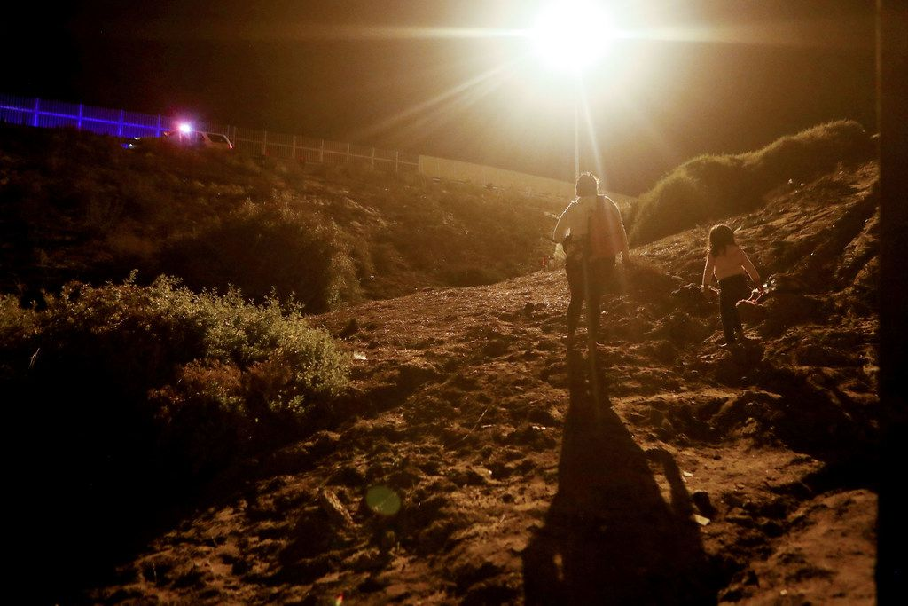 Honduran migrants walk on the U.S. side of the U.S.-Mexico border fence after crossing the fence as a Border Patrol vehicle waits.