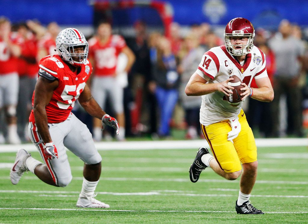 USC Trojans quarterback Sam Darnold (14) scrambles as Ohio State Buckeyes defensive lineman Tyquan Lewis (59) chases after him during the second half of play in the Cotton Bowl at AT&T Stadium in Arlington, Texas on Friday, December 29, 2017. Ohio State Buckeyes defeated USC Trojans 24-7. (Vernon Bryant/The Dallas Morning News)