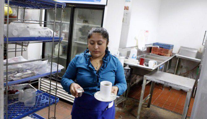 Yolanda Romero lleva café a clientes de un restaurante salvadoreño en el sur de Irving. Los hispanos son el 41% de la población en Irving, y el ayuntamiento quiere que den su opinión sobre el futuro de su ciudad. (ESPECIAL PARA AL DÍA/BEN TORRES)