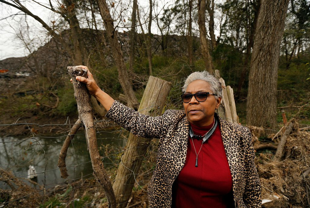 Homeowner Marsha Jackson stands alongside the flood-damaged fencing bordering a large hill of recycled roof shingles (in background) near State Highway 310 and Interstate 20 in southern Dallas.
