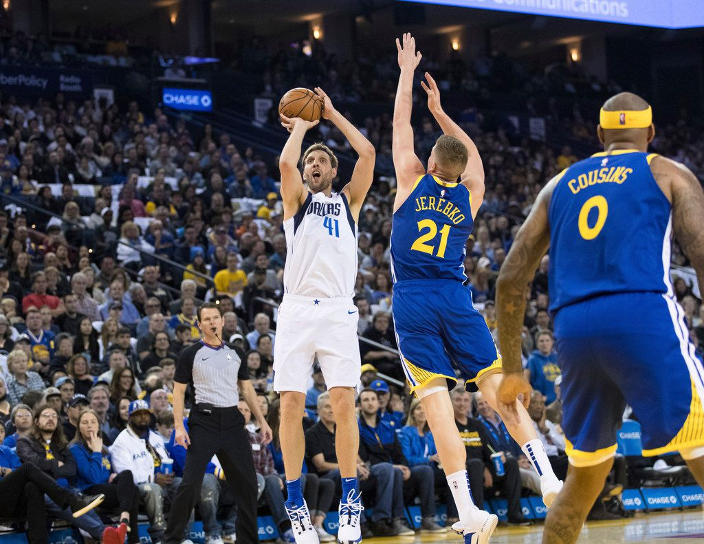 Dallas Mavericks forward Dirk Nowitzki (41) shoots as Golden State Warriors forward Jonas Jerebko (21) defends in the first half of an NBA basketball game Saturday, March 23, 2019, in Oakland, Calif. (AP Photo/John Hefti)