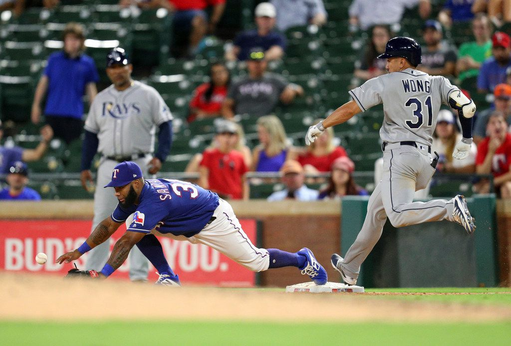 Texas Rangers' second baseman Danny Santana (38) comes off the bag to reach the ball thrown by pitcher Emmanuel Clase as Tampa Bay Rays' Kean Wong (31) is safe at first during the 11th inning of a baseball game Tuesday, Sept. 10, 2019, in Arlington, Texas. Clase was charged with an error. (AP Photo/Richard W. Rodriguez)