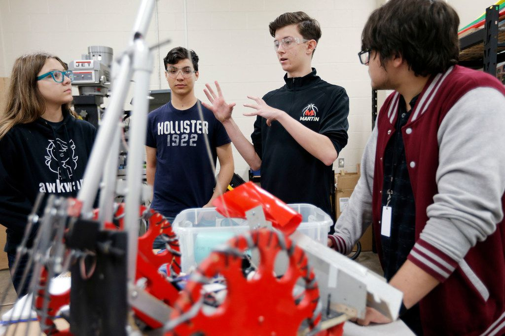 Arlington Martin students Olivia Maness, 14, (from left) Camden Johnson, 16, Benjamin Kocurek, 15, and Brandon Munoz, 14, discuss how they are going to design a robot that will aid in a simulated fire suppression and rescue scenario in a competition scheduled for October.