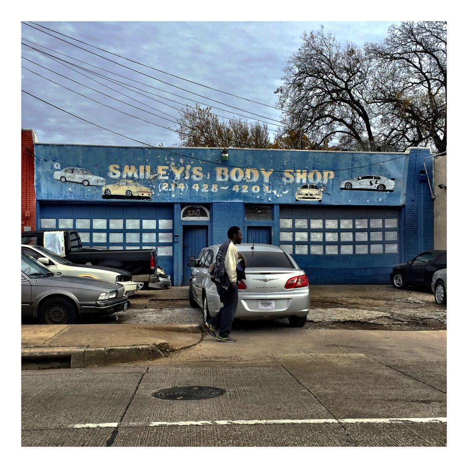 A man walks past Smiley's Body Shop on South Second Avenue in South Dallas.