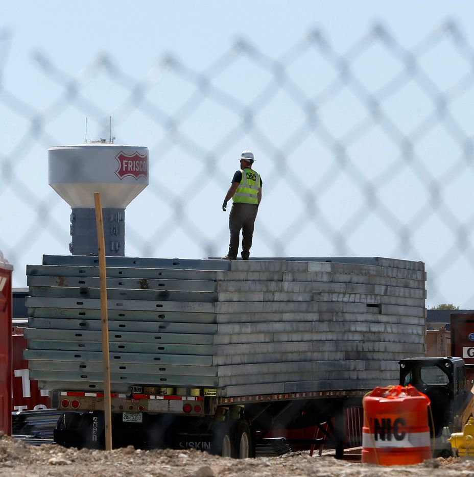 A construction worker stands on a heap of steal during construction in Frisco Station in Frisco on Thursday.
