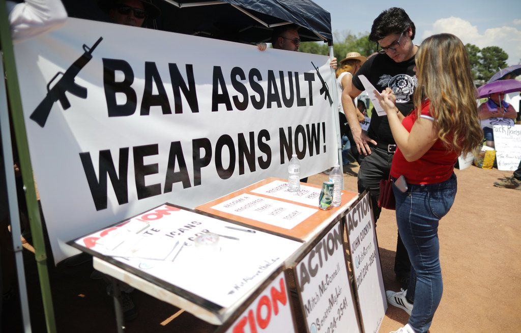 """A """"Ban Assault Weapons Now"""" sign was displayed near a voter registration table at a protest against President Donald Trump's visit on Aug. 7 following a mass shooting which left at least 22 people dead in El Paso."""