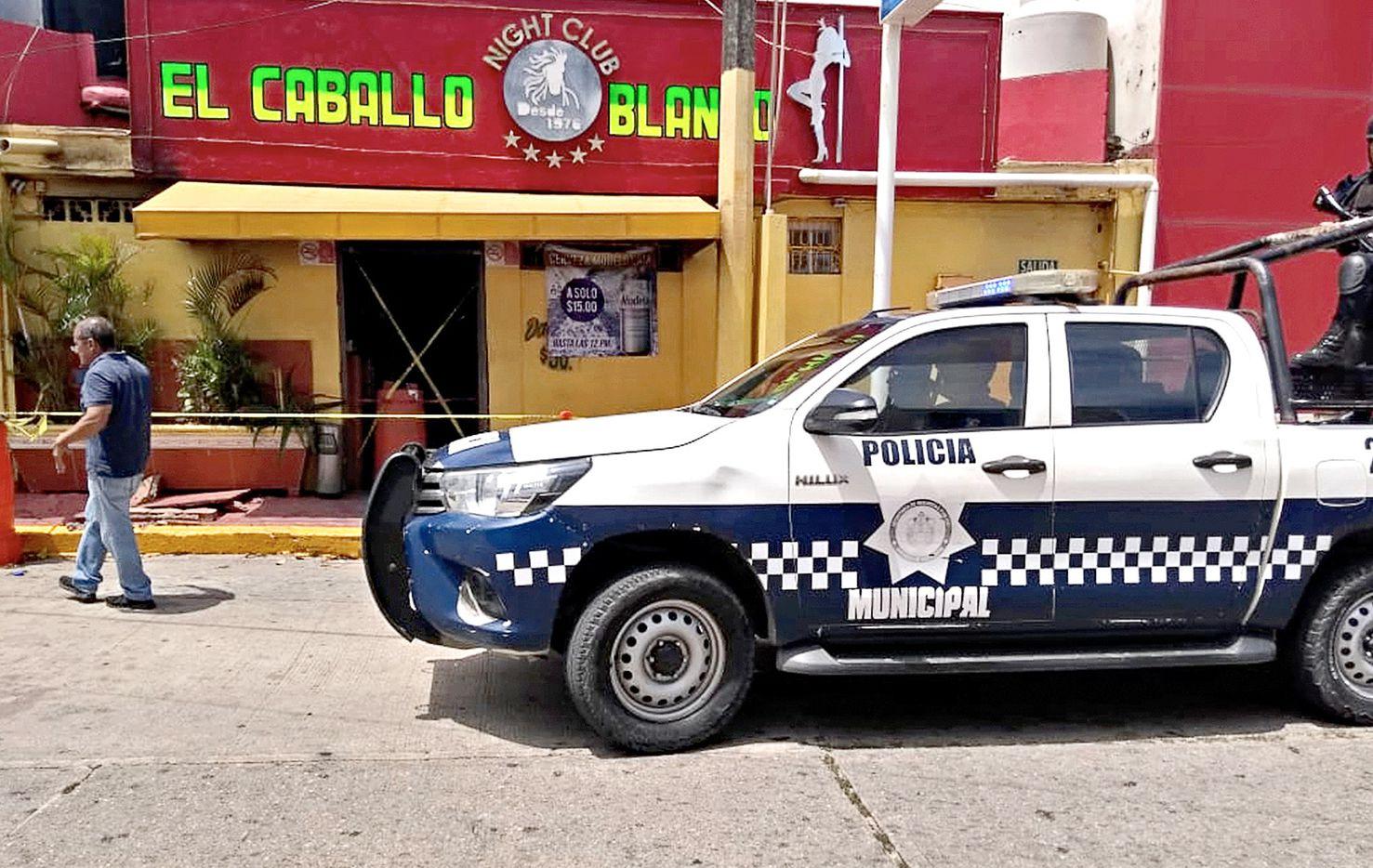 Un vehículo de la Policía de Veracruz vigila el bar en Coatzacoalcos, donde un ataque cobró la vida de al menos dos decenas de personas.