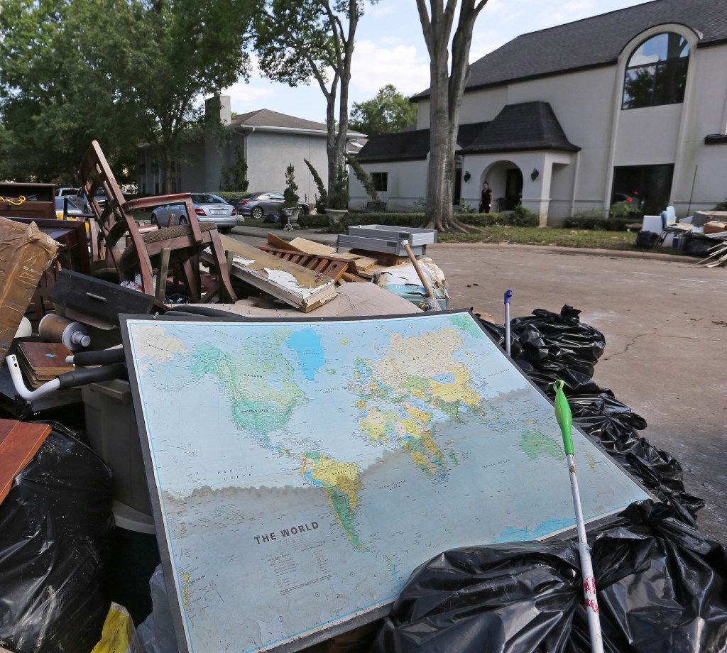 A map of the world shows the waterline of the flood waters as it sits in the trash outside the Singh home in the Memorial Drive Acres subdivision, which was flooded as a result of water released from a dam, photographed on Sunday, September 10, 2017. (Louis DeLuca/The Dallas Morning News)