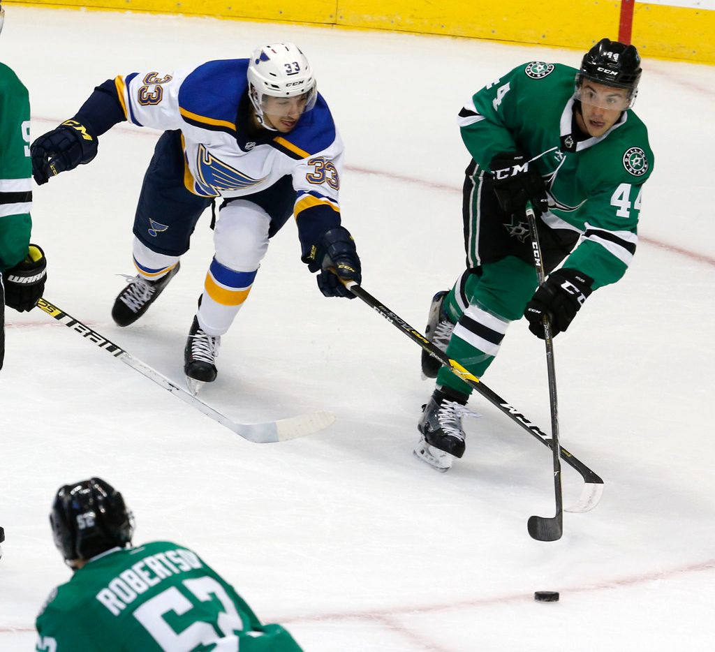 Dallas Stars defenseman Gavin Bayreuther (44) and St. Louis Blues right wing Jordan Kyrou (33) fight for the puck during the first period of their hockey game at American Airlines Center in Dallas on Sept. 18, 2018.  (Nathan Hunsinger/The Dallas Morning News)