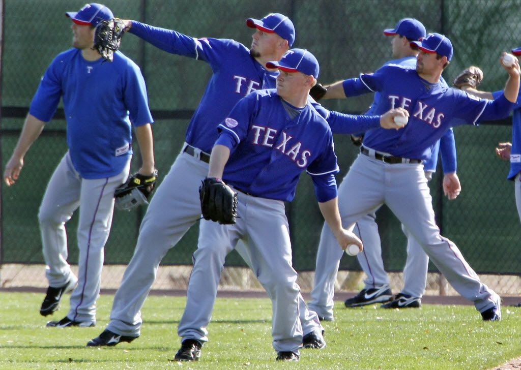 Texas Rangers pitchers, including Kasey Kiker, front, warm up along the foul line at Texas Rangers  spring training camp in Surprise, AZ, on Wednesday, March 3, 2010.   (Louis DeLuca/The Dallas Morning News)