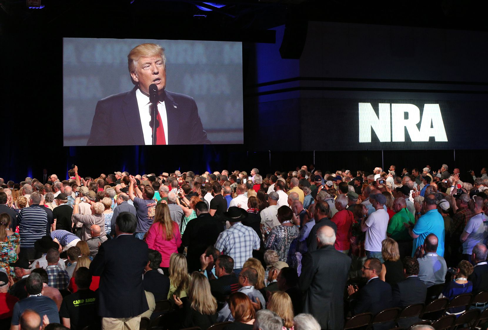Thousands of NRA attendees watch the keynote by President Donald J. Trump on one of the giant screens in Hall A at the NRA-ILA Leadership Forum on Friday, April 28, 2017, in Atlanta.