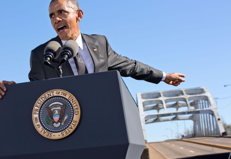 The President points towards the Edmund Pettus Bridge during his speech in Selma, Ala.