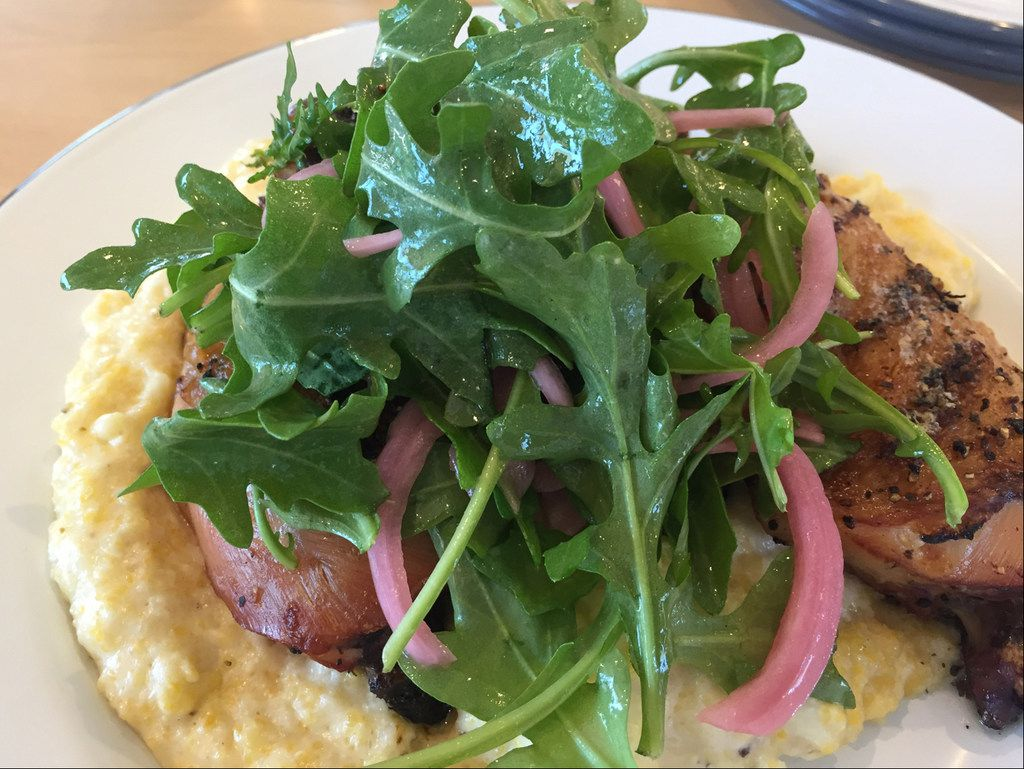 The yardbird and grits at The Market at Bonton Farms includes a char-broiled hind chicken quarter nested on top of rustic Anson Mills grits and garnished with arugula and pickled onions in Dallas. (Irwin Thompson/The Dallas Morning News)