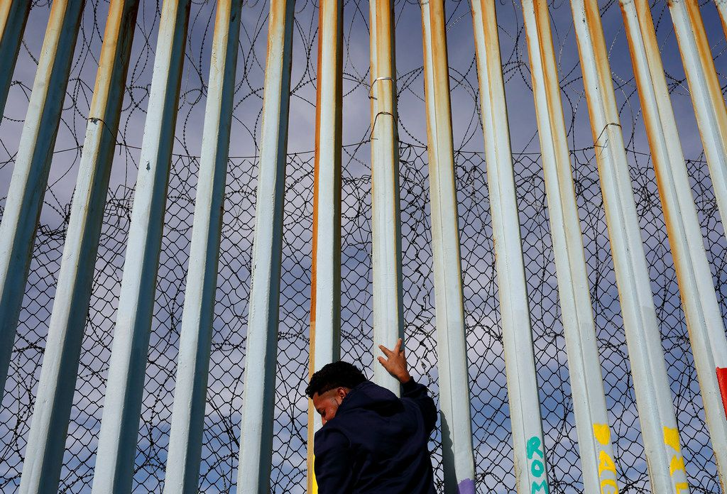 A man holds on to the border wall along the beach on Jan. 8, 2019, in Tijuana, Mexico. Ready to make his case on prime-time TV, President Donald Trump is stressing humanitarian as well as security concerns at the U.S.-Mexico border as he tries to convince America that he must get funding for his long-promised border wall before ending a partial government shutdown that has hundreds of thousands of federal workers facing missed paychecks.