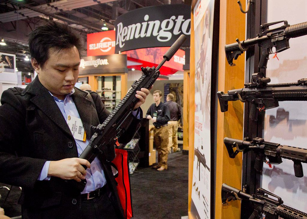 Accessories manufacturer Kevin Kao, of Irvine, Calif., examines a military grade Remington Adaptive Combat Rifle at the 35th annual SHOT Show in Las Vegas. U.S. gun maker Remington Outdoor Company filed for bankruptcy protection, after years of falling sales and lawsuits tied to the Sandy Hook Elementary School massacre.
