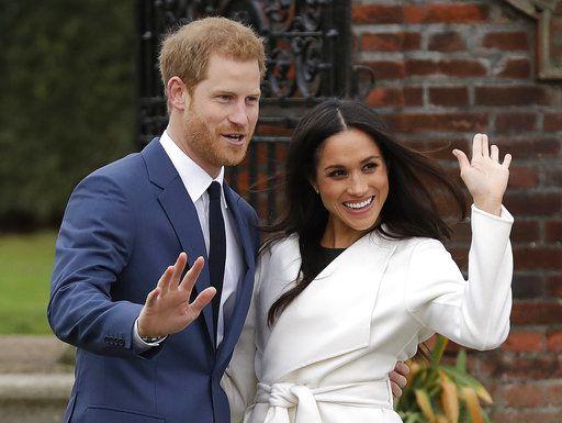 El príncipe Enrique de Inglaterra y su prometida, la actriz estadounidense Meghan Markle, miran su anillo de compromiso al posar para la prensa en el Palacio de Kensington, en Londres, el lunes 27 de noviembre del 2017. (AP Foto/Matt Dunham)