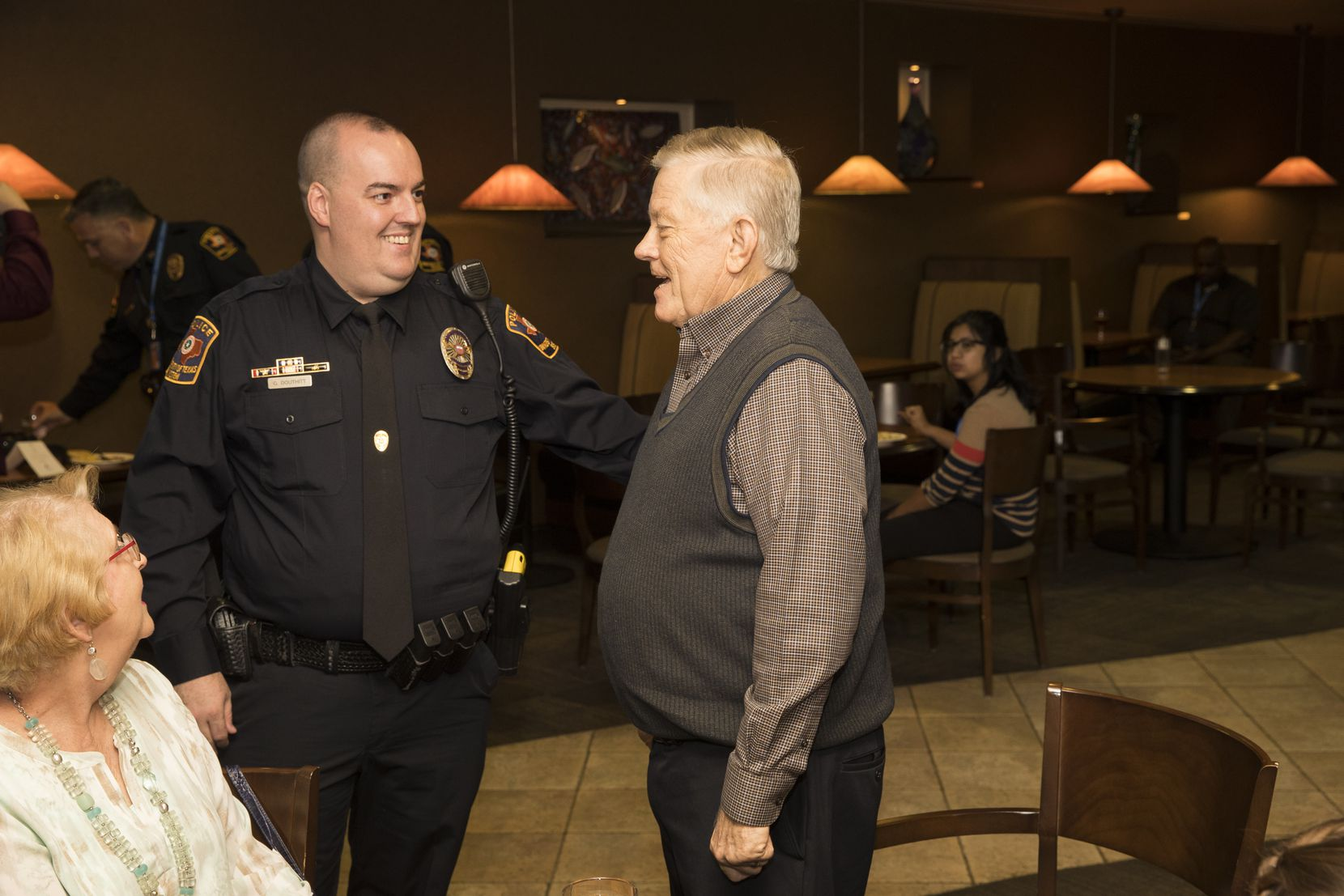 UTA police Officer Garry Douthitt chats with James Gamble during a ceremony at the University of Texas at Arlington recognizing Douthitt and others for helping save Gamble's life after he had a heart attack on campus.
